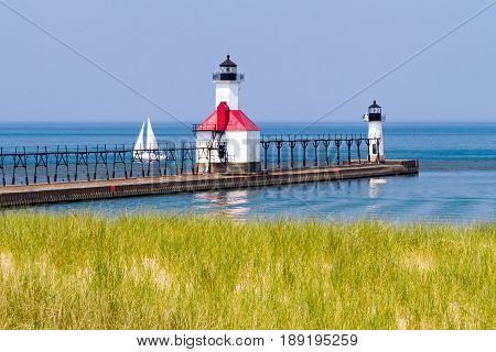 St. Joseph Michigan North Piewr LIghthouses with a Sailboat on Lake Michigan.