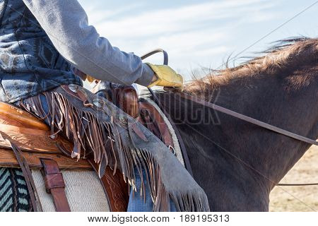 close up of a cowboy on a horse wearing chaps