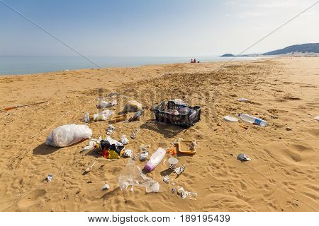 Karpasia, Cyprus - 10 May, 2017: Garbage on the beautiful Golden beach in Karpasia Cyprus near Apostolos Andreas monastery with two people in the distance
