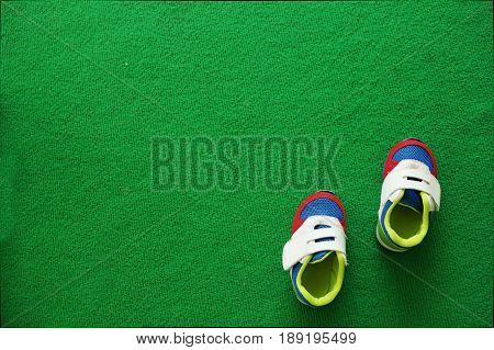 Baby boy shoes on a green carpet background. Football field
