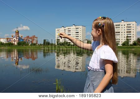 A girl of seven years points to the distance by the lake