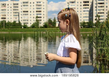 A seven-year-old is looking into the distance by the lake