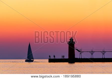 A vividly colorful twilight sky silhouettes a sailboat people and the lighthouse at South Haven Michigan on Lake Michigan.