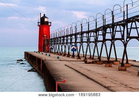 The vivid red South Haven Lighthouse with elevated metal catwalk approach structure is backed by a colorful morning sky over Lake Michigan.