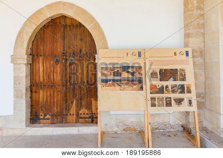 Karpasia, Cyprus - 10 May, 2017: Apostolos Andreas monastery restoration description boards and restored door. The historic Apostolos Andreas Monastery is located in the Karpasia peninsula north-east Cyprus.