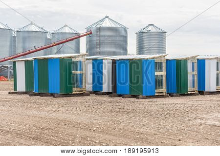 striped tin bee hut shelters in front of some graineries