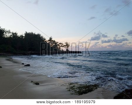 Beautiful Dusk over the ocean with waves moving to shore on the North Shore of Oahu.