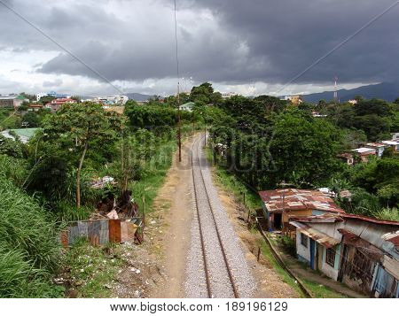 SAN JOSE COSTA RICA - JULY 13: Train tracks run into the distance though neighborhood on a cloudy day taken July 13 2009 Downtown San Jose Costa Rica.