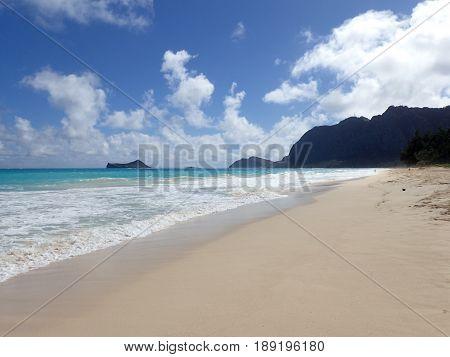 Gentle wave lap on Waimanalo Beach looking towards Rabbit island and Rock island on a nice day Oahu Hawaii. January 2017.