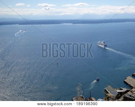SEATTLE-- JUNE 25: Aerial view of Puget Sound with boats leaving harbor Large Ferris Wheel Wharf and Highway on June 25 2016 in Seattle WA.