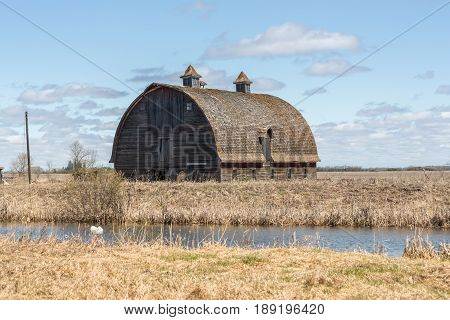 old rustic barn beside a water filled ditch