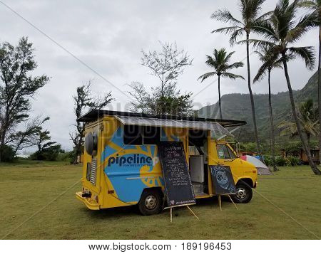 OAHU - APRIL 22 2017: Yellow Pipeline Fresh Pressed Cane Juice Food Truck powered with Solar Panels in grass field with ironwood and coconut trees on Earth Day.