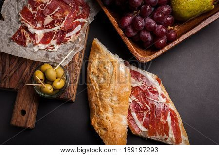 Jamon Iberico with white bread, olives on toothpicks and fruit on a dark background. Top view.