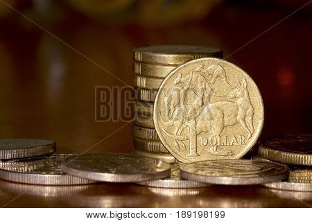 Australian one dollar coin in a stack.