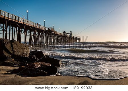 OCEANSIDE, CALIFORNIA - MARCH 23, 2017:   Waves and boulders at the base of the Oceanside fishing pier in San Diego County.