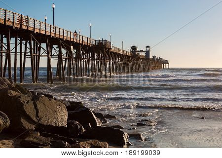 OCEANSIDE, CALIFORNIA - MARCH 23, 2017:  The landmark Oceanside waterfront fishing pier at dusk with boulders at its base.