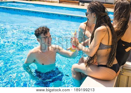 Party at smimming pool. Group of cheerful couples drinking cocktails in the pool. Man gets to know a woman