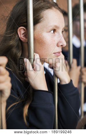 Young sad and boredom schoolgirl holding at the gate