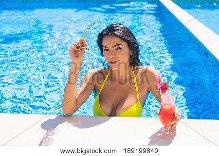 portrait of young sexy girl at swimming pool, wearing bikini. She is putting off sunglasses and looking at camera. drinking red cocktail during vacation. Pool party