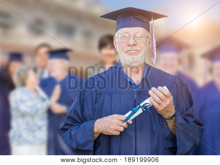 Proud Senior Adult Man In Cap and Gown At Outdoor Graduation Ceremony.