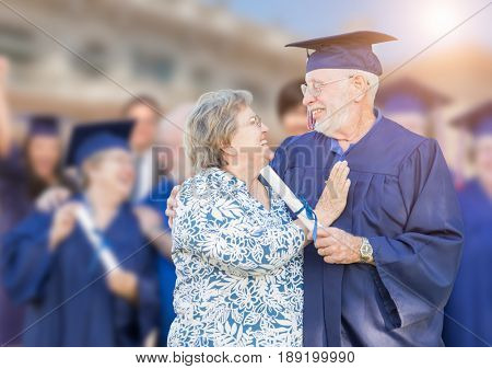 Senior Adult Male In Cap and Gown Being Congratulated By Wife At Outdoor Graduation Ceremony.