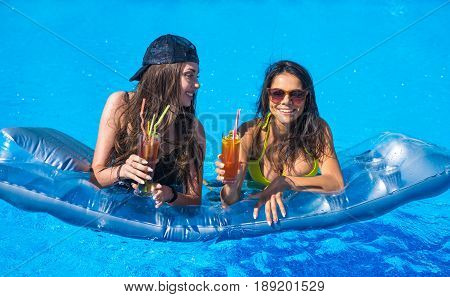 Party at smimming pool. Group of cheerful girls on swimming mattress or air mattress in the swimming pool drinking cocktails and laughing