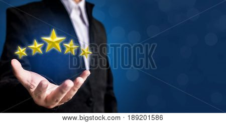 Review increase rating or ranking evaluation and classification concept. Businessman hand holding yellow five stars