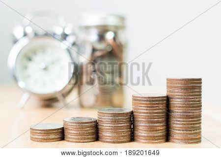 Coin stack step growing up to success financial business with clock and jar Save money and investment concept