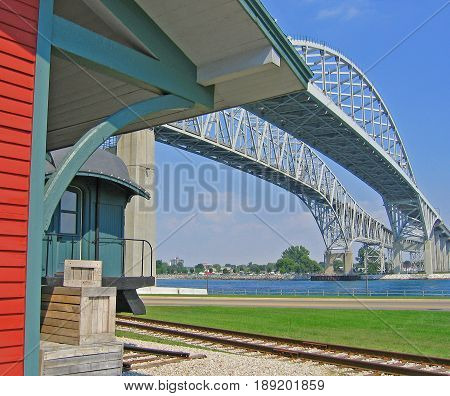 Standing beside the Blue Water International Bridge, which carries vehicular traffic across the St. Clair River from Port Huron, Michigan, USA to Sarnia, Ontario, Canada, is the historic Fort Gratiot train depot, built in 1858, and a restored baggage car.