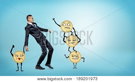 A businessman losing his balance while many large golden coins with arms and legs are trying to make him fall. Hard earned money. Financial pitfalls. Small and big profits.