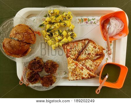 Burger,kawab, gujarati khandvi, chees sandwich with onion and green chilli sauce on tray with green backgroung as complete breakfast.