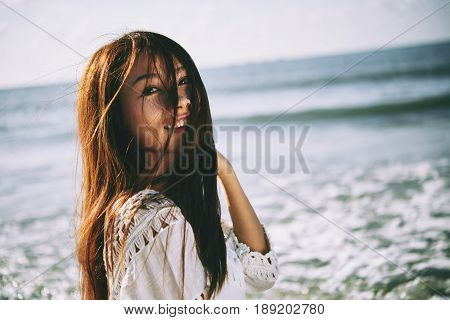 Portrait of pretty cheerful girl with hair fluttering in the wind standing on beach