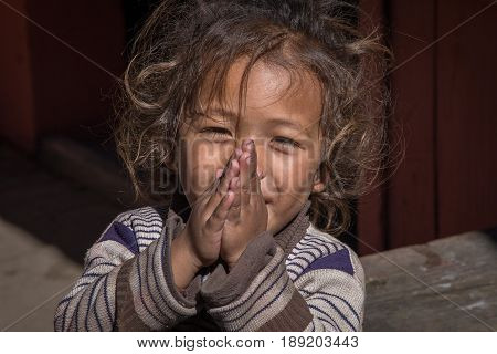 MANANG VILLAGE WESTERN NEPAL - OCTOBER 14 2016 : Portrait young girl with folded hands in street . Close up