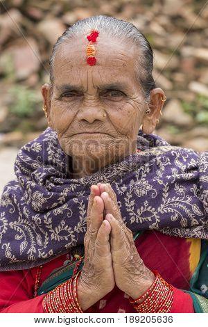 KATHMANDU NEPAL - SEPTEMBER 29 2016 : Portrait old woman in traditional dress with folded hands in street Kathmandu Nepal. Close up
