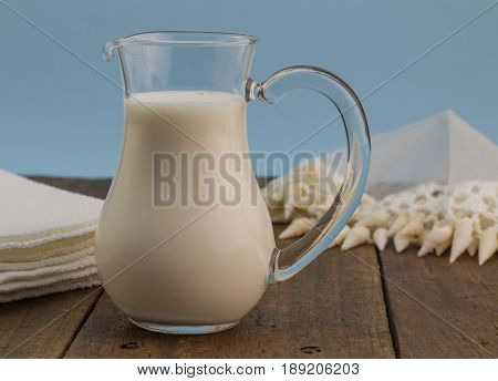 Fresh whole-milk in glass jug on rustic wooden table with jug cover and cloth in background