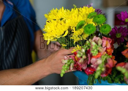 Mid section of florist holding bunch of flower in florist shop