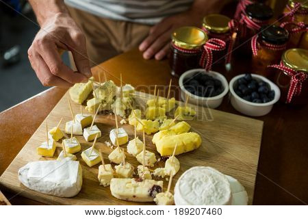 Close-up of staff arranging piece of cheese on wooden board in grocery shop
