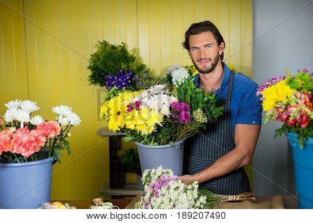 Portrait of happy florist holding bucket of flower in florist shop