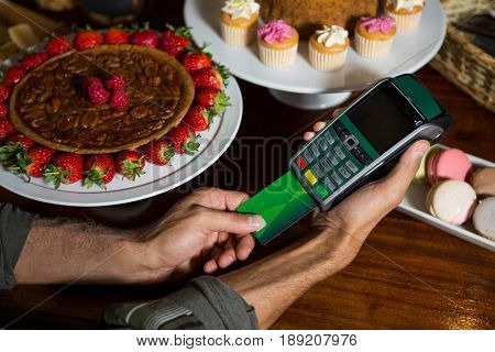 Customer making payment through credit card at counter in coffee shop