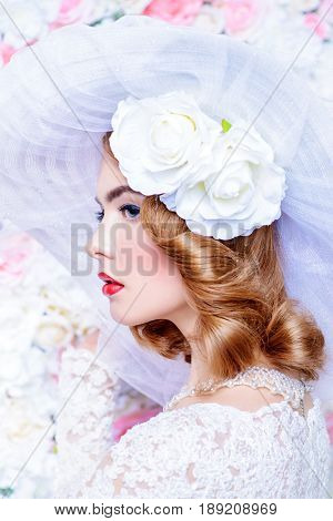 Portrait of a beautiful bride woman in elegant lace dress and broad-brimmed hat posing over floral background. Wedding. Beauty, fashion concept.