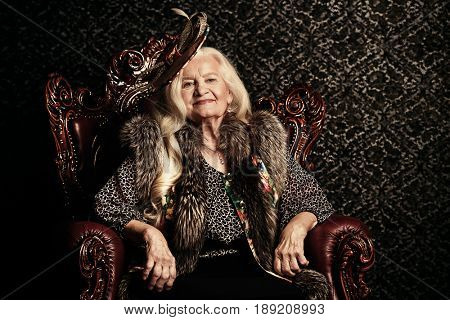 Fashionable old woman with beautiful blonde hair and elegant hat posing in vintage interior. Beauty, fashion. Retro style.