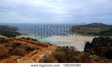 Stunning bright views of the famous Bay of Balos in Crete. Destroyed bright brown wall in foreground, the sea and the ship in the distance