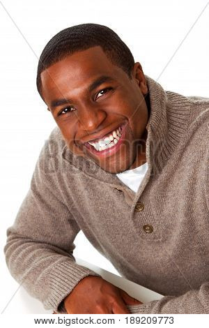 Happy African American man sitting with his arms crossed.
