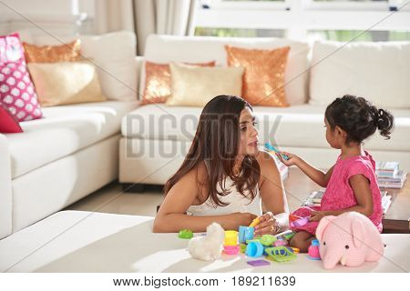 Little girl pretending to feed her mother