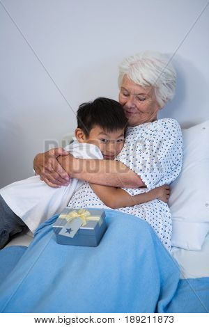 Boy giving a hug to senior patient on bed at hospital