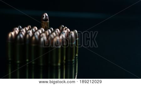 Smiling weapon. 9mm bullets on the black mirror background