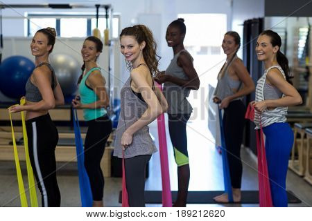 Portrait of smiling women performing stretching exercise with resistance band in gym