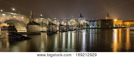 Charles Bridge and buildings along the Vltava at night, in Prague, Czech Republic.