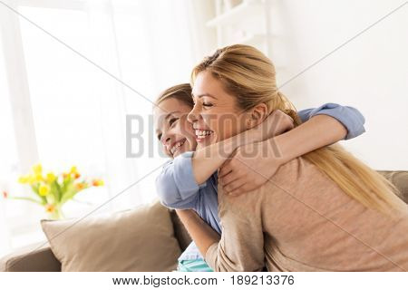 people and family concept - happy smiling girl with mother hugging on sofa at home