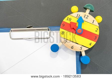 Back to school background with books and alarm clock over clipboard